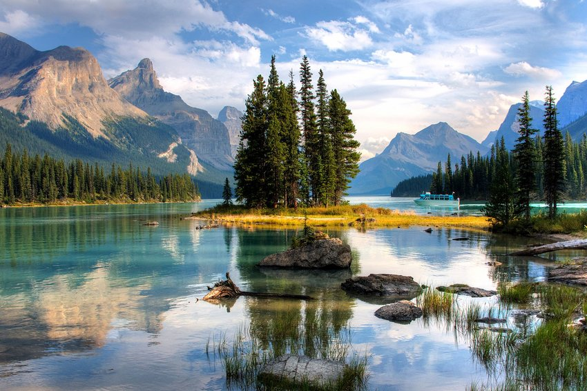 Photo of an idyllic lake scene with pine trees and mountains