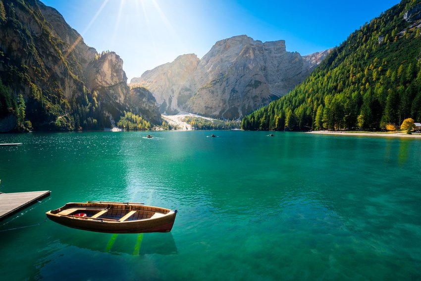 Photo of a rowboat on a lake surrounded by trees and mountains