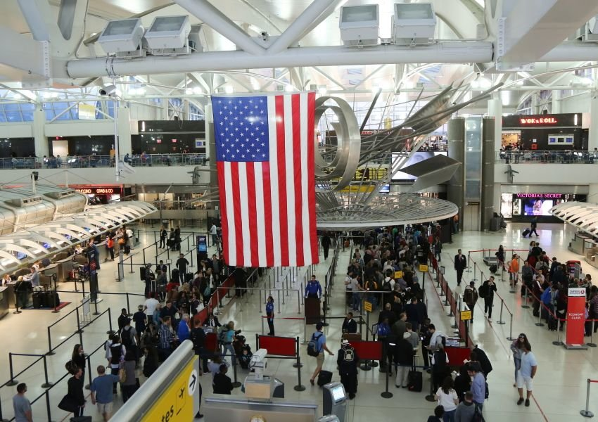 Crowded airport with an American flag hanging from ceiling