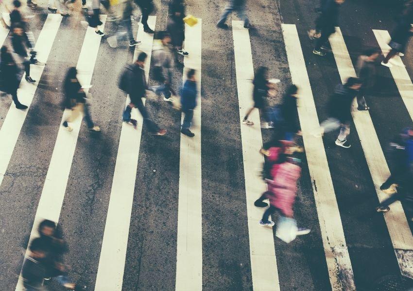 Busy crosswalk with people rushing across