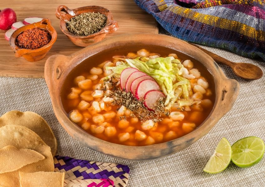 Photo of Pozole with tortilla chips, lime, and seasonings