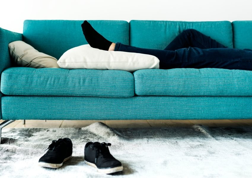 Photo of man's legs on a couch with shoes on the floor