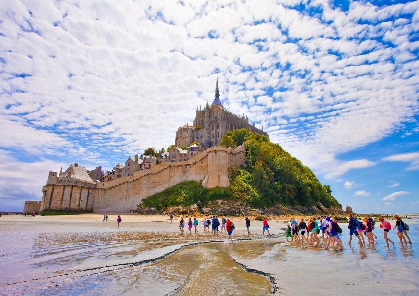 Photo of people walking in front of Mont Saint-Michel