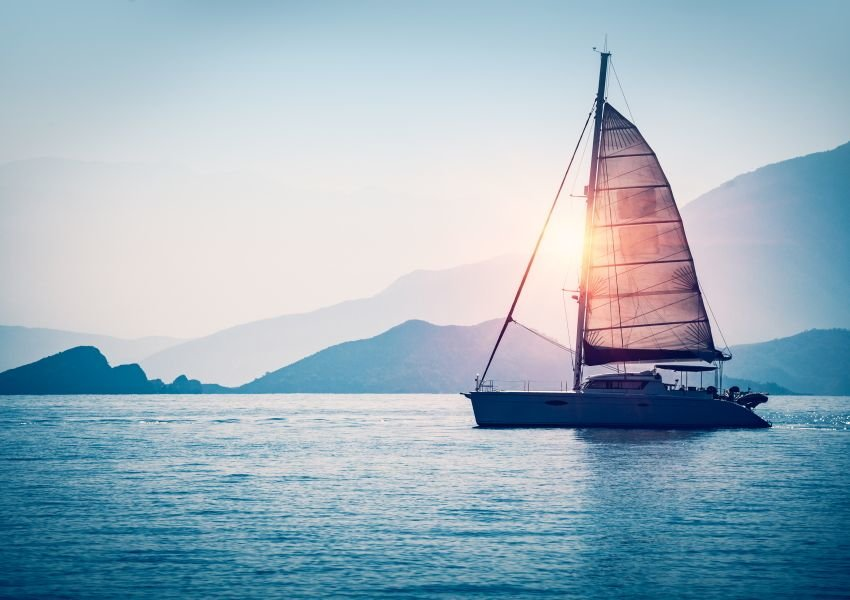 Photo of a sailboat on the water with mountains in the background