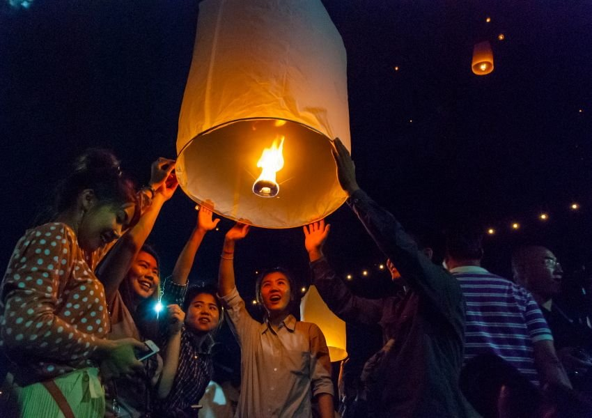 Young people lifting a lit lantern