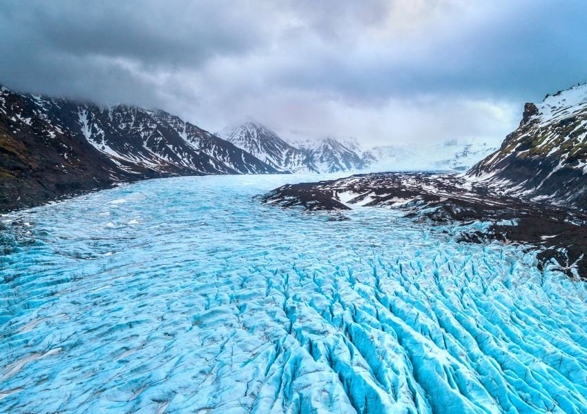 Photo of a huge glacier surrounded by snowcapped mountains