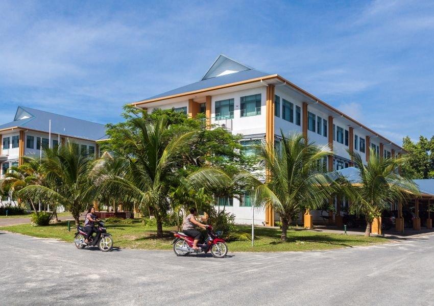 Photo of people on motorbikes passing buildings in Funafuti