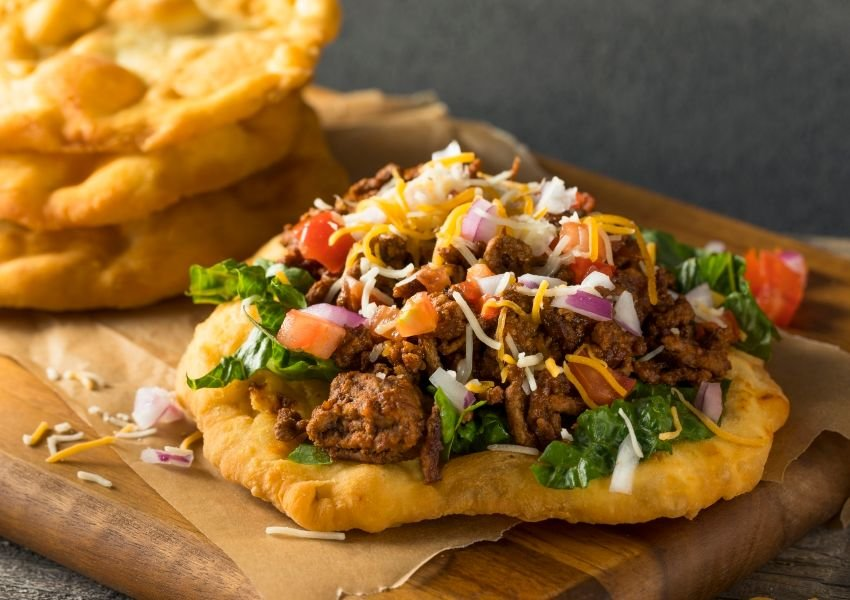 A Navajo taco with ground meat, cheese, and vegetables