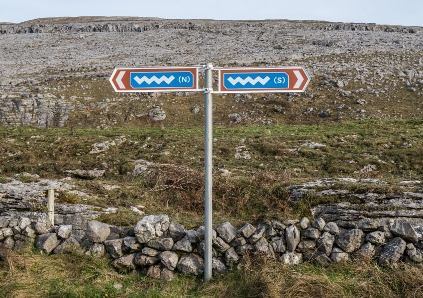 Road sign in Ireland depicting a wavy pattern on a blue and brown background