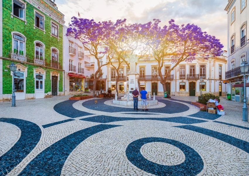 Photo of a city plaza with blue and white cobblestone pavement, colorful buildings, and trees with purple leaves