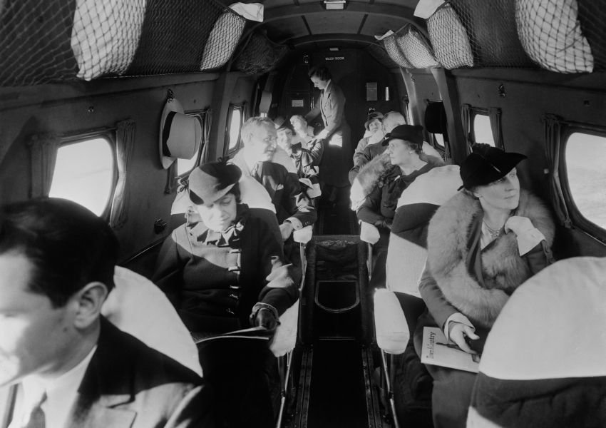 Black and white vintage photo of well-dressed passengers on an airplane