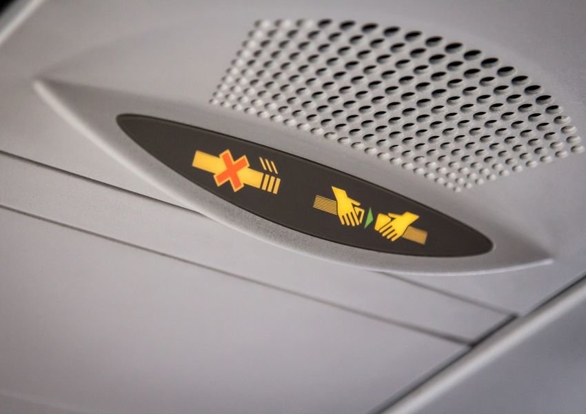 "Photo of the ""no smoking"" and ""fasten seatbelt"" signs on an airplane"