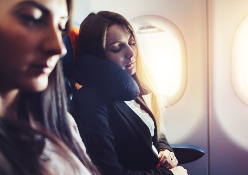Photo of a woman sleeping with a neck pillow in an airplane seat