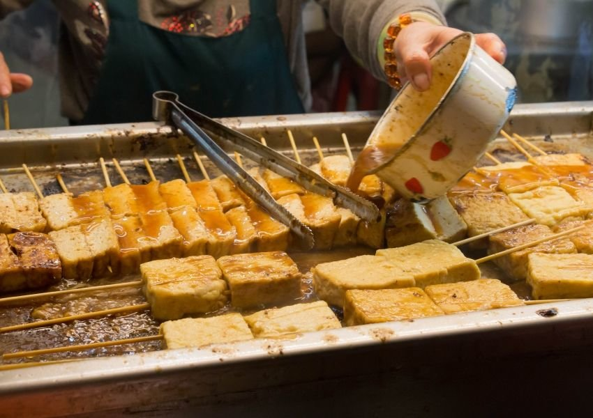 Photo of tofu pieces on sticks with a person pouring sauce over them