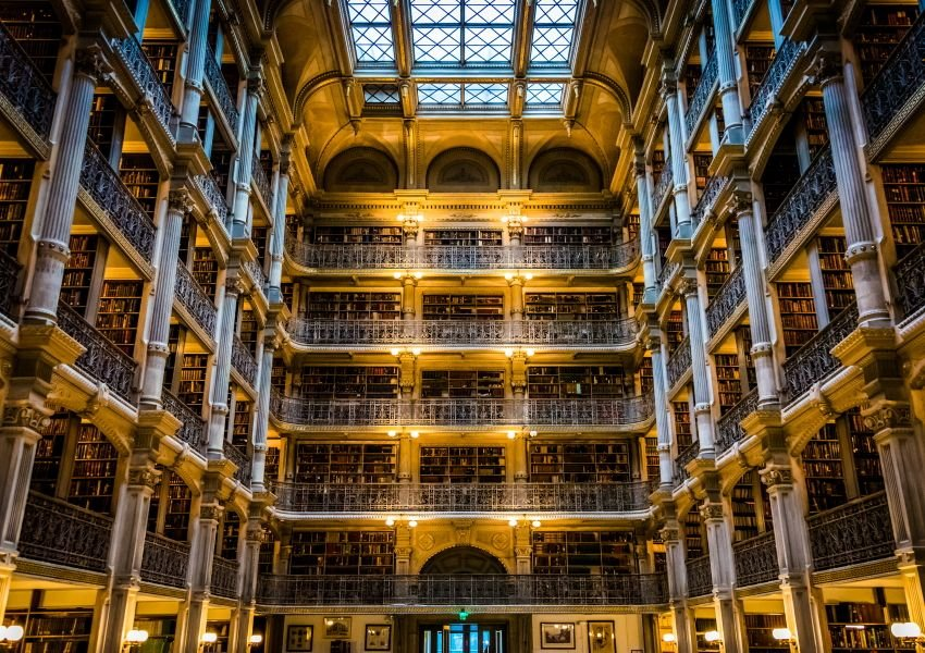 Photo of elegant, tall atrium with thousands of books on shelves