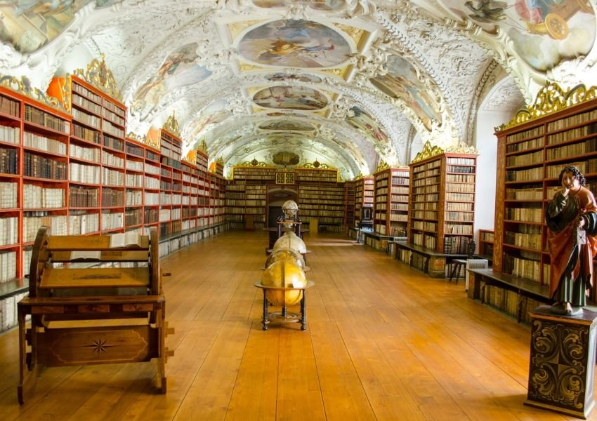 Photo of a room inside an elegant old library with frescoed ceilings and old statues