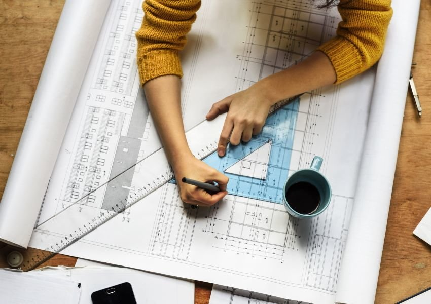 Photo of a pair of hands drawing an architecture blueprint