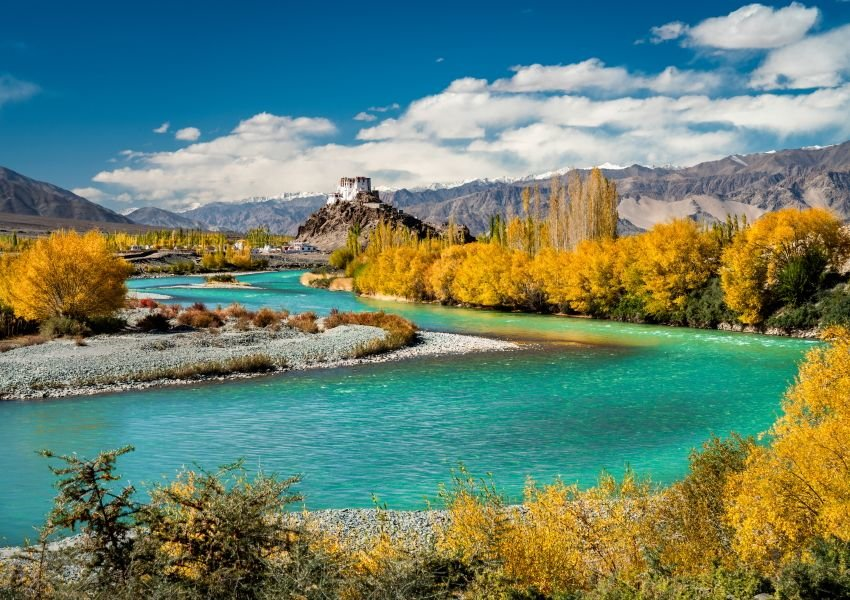 Photo of a bright blue river running through yellow trees and mountains