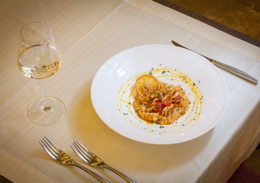 Photo of a bowl of risotto with silverware and a glass of white wine