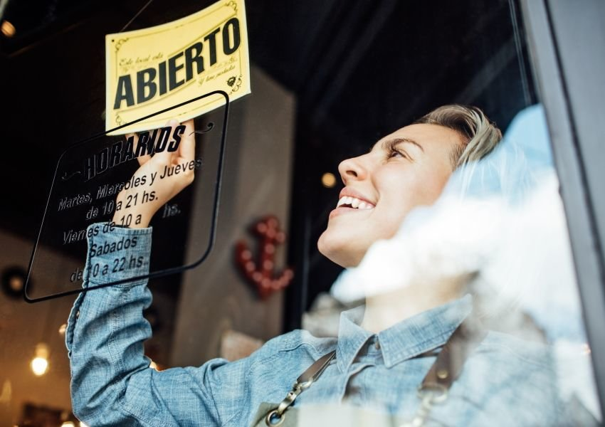 Woman flipping a Spanish sign in a storefront