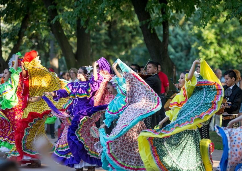 Women in bright beautiful dresses dancing in unison
