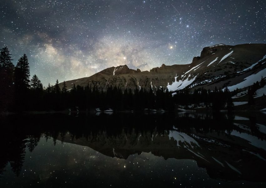 Photo of a starry night sky in front of mountains and a lake