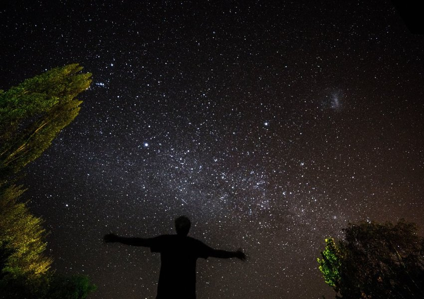 Photo of a person's silhouette against a starry night sky