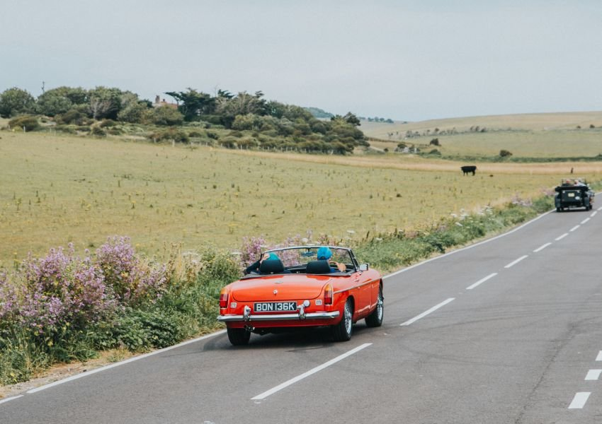 Photo of an orange car driving on the left side of a rural road