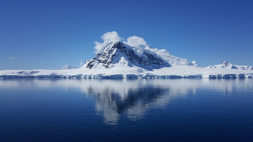 Photo of a mountain and icebergs in Antarctica