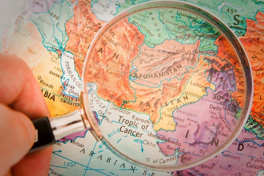 Close-up photo of a magnifying glass above a map of the Middle East