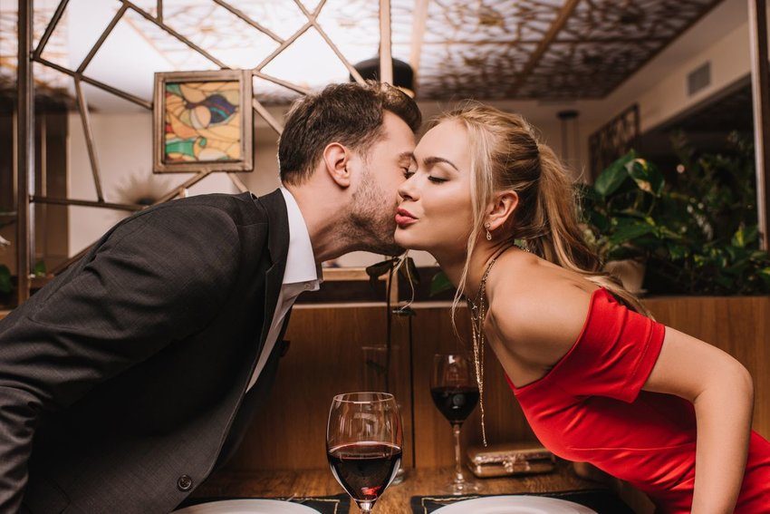 Photo of a man kissing a woman on the cheek in a formal restaurant