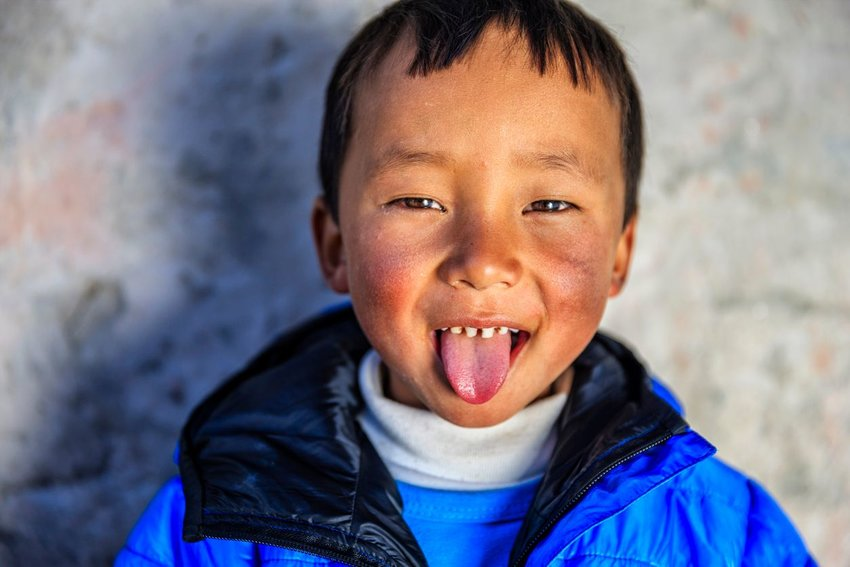 Photo of a young boy sticking out his tongue