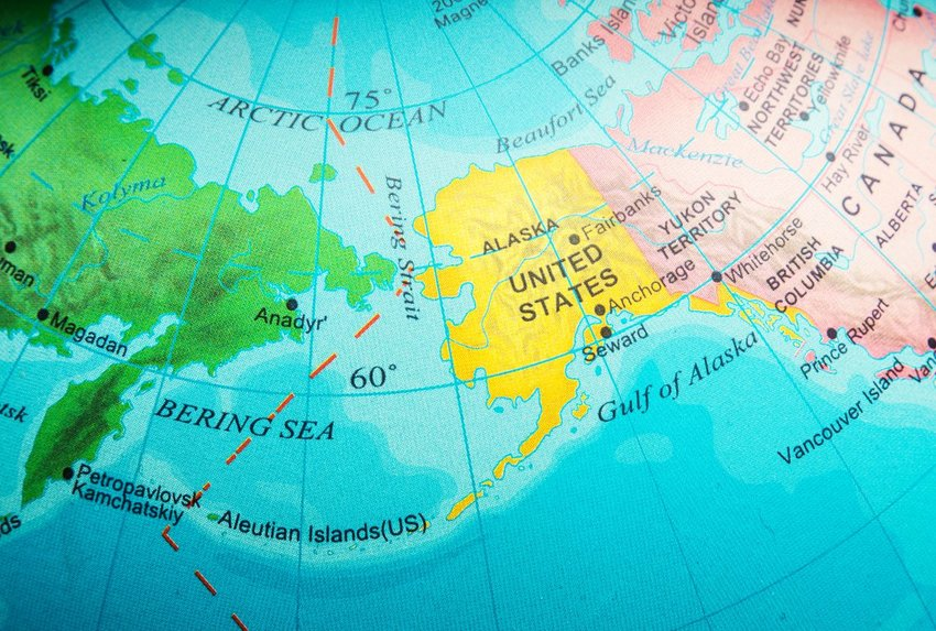 Photo of a map displaying a dotted line between Russia and Alaska