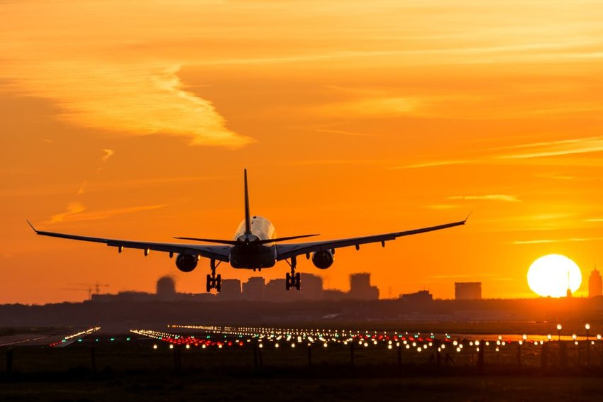 Airplane descending onto runway during gorgeous evening sunset