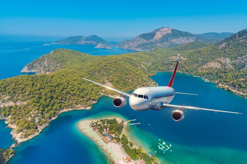 Airplane rising into the sky against background of islands and blue ocean