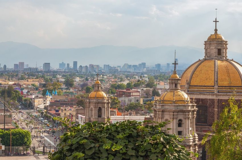 Aerial view of the Old Basilica of Guadalupe during the day with Mexico City skyline in background