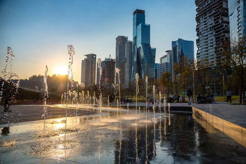 Water fountains in wealthy area of Park Parque in Mexico City with sunset in background