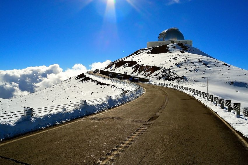 The snowy Mauna Kea Observatory during the day with long, winding road in foreground
