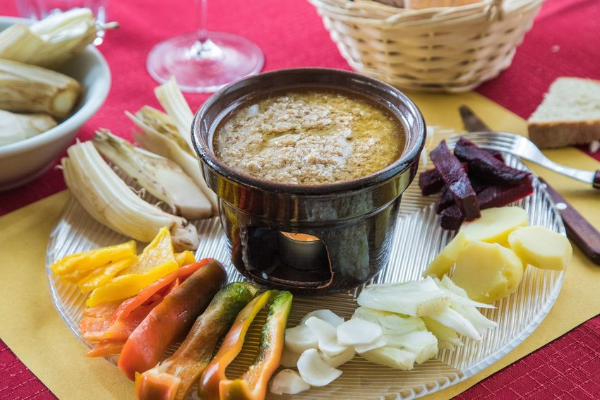 Bagna cauda appetizer with olive oil, garlic, and roasted peppers on serving tray