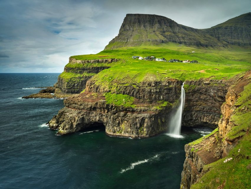 Aerial view of Faroe Island waterfall with mountains and storm clouds in background