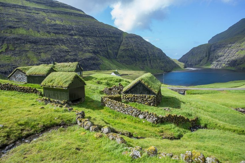 Nordic dwellings dotting Faroe Islands countryside, with cliffs and clouds in background, Denmark