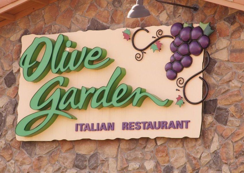Up close view of Olive Garden sign and logo against a rock wall