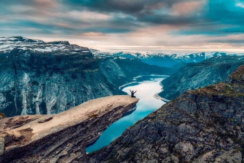 Aerial landscape of Trolltunga with hiker sitting on cliff's edge, Rogaland, Norway