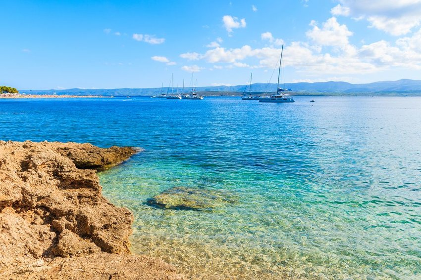 View of Zlanti Rat blue waters and boats near Brac island, Croatia