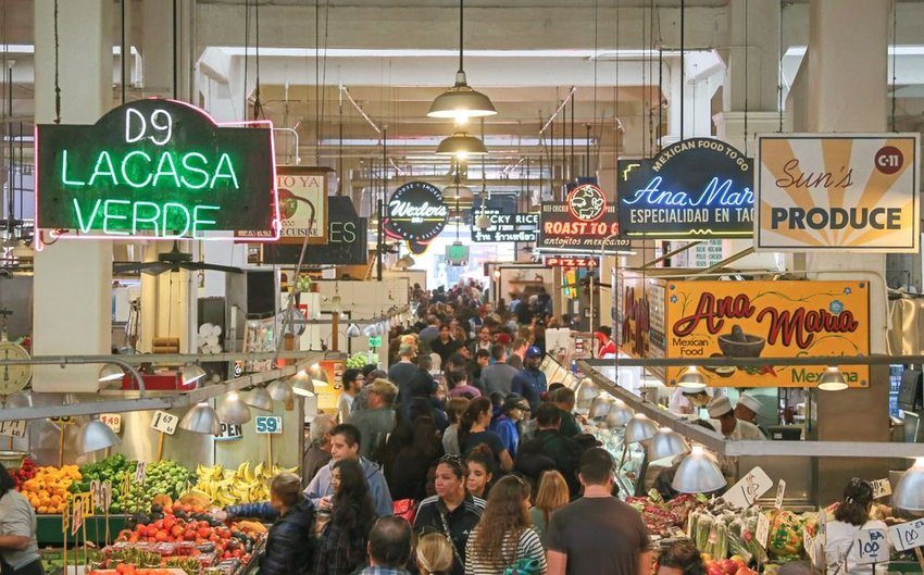 Photo of a busy marketplace full of people and produce stands