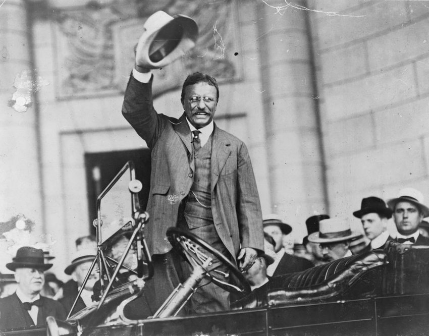 Old black and white photo of Theodore Roosevelt smiling and raising his hat