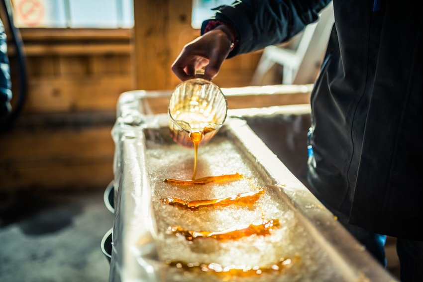 Photo of someone pouring maple syrup over snow