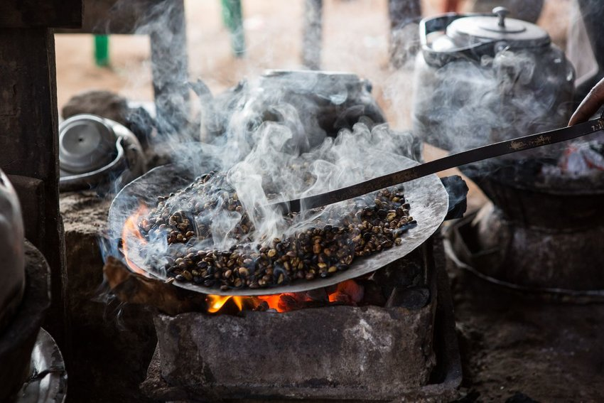 Photo of coffee beans roasting over a fire