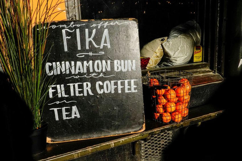 "Photo of a menu board outside a coffee shop displaying the words ""fika,"" ""cinammon bun,"" ""filter coffee,"" and ""tea"""