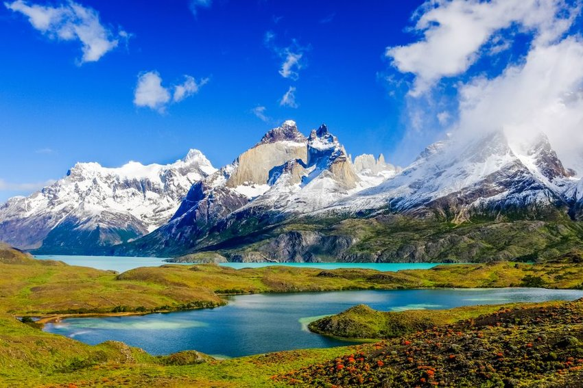 Photo of jagged snow-covered mountains behind lakes and grassy plains